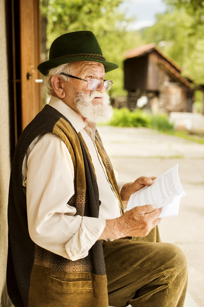 Old man reading the newspaper in front of his house