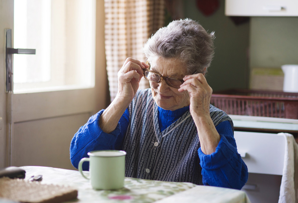 Old woman is drinking tea in her country style kitchen