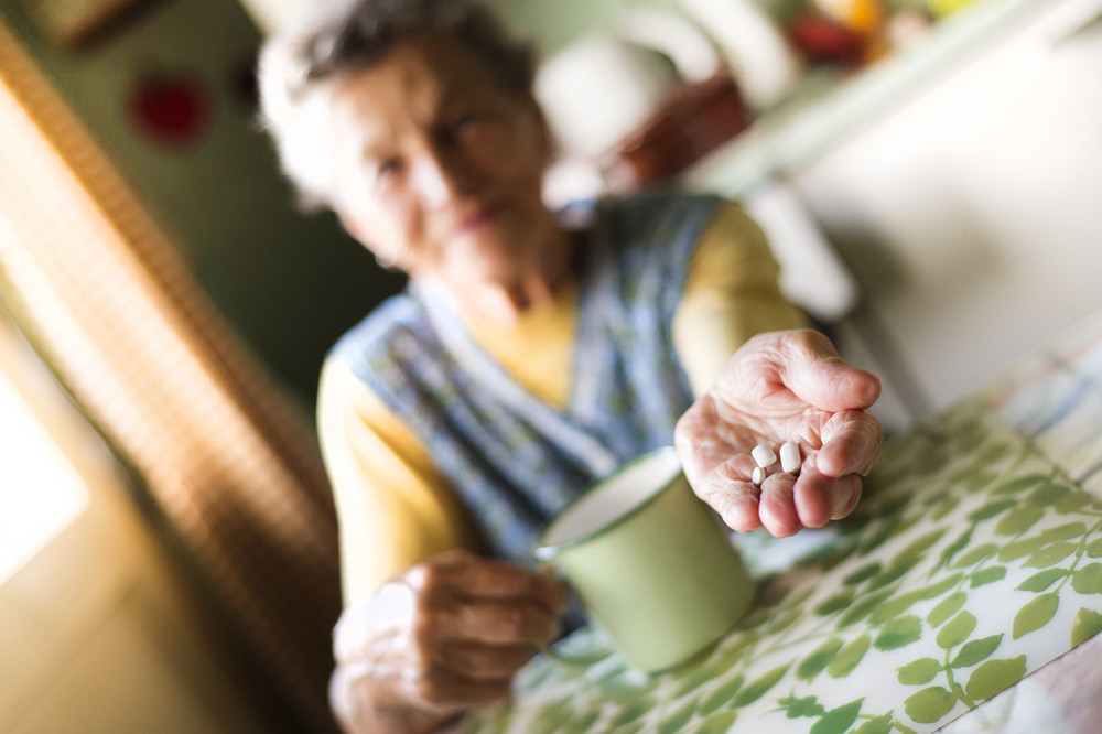 Old woman is taking pills in her country style kitchen