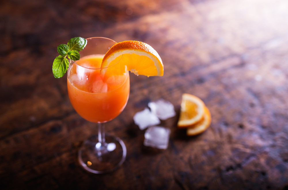 Orange juice in glass with mint and fresh fruit. Studio shot on wooden background.