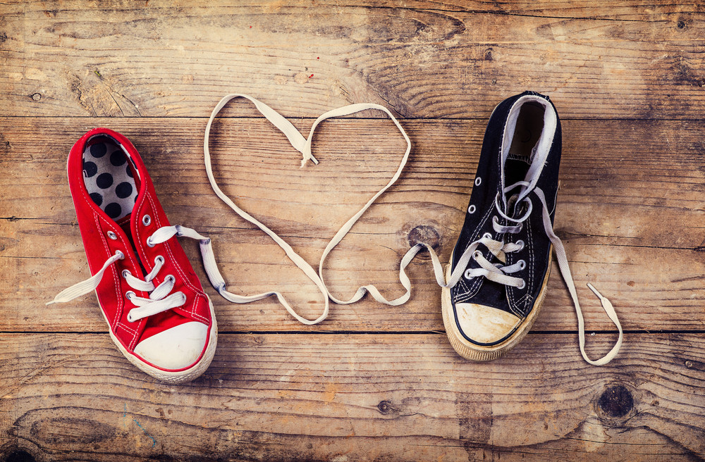 Original Valentine's Day love concept with red and black sneakers. Studio shot on a wooden floor background.
