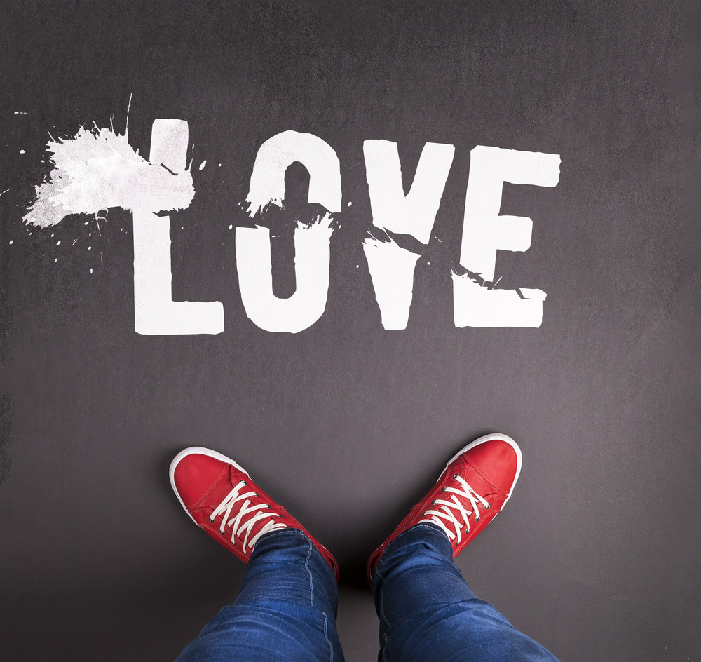 Original Valentine's Day love concept with red sneakers and chalk drawn love title.