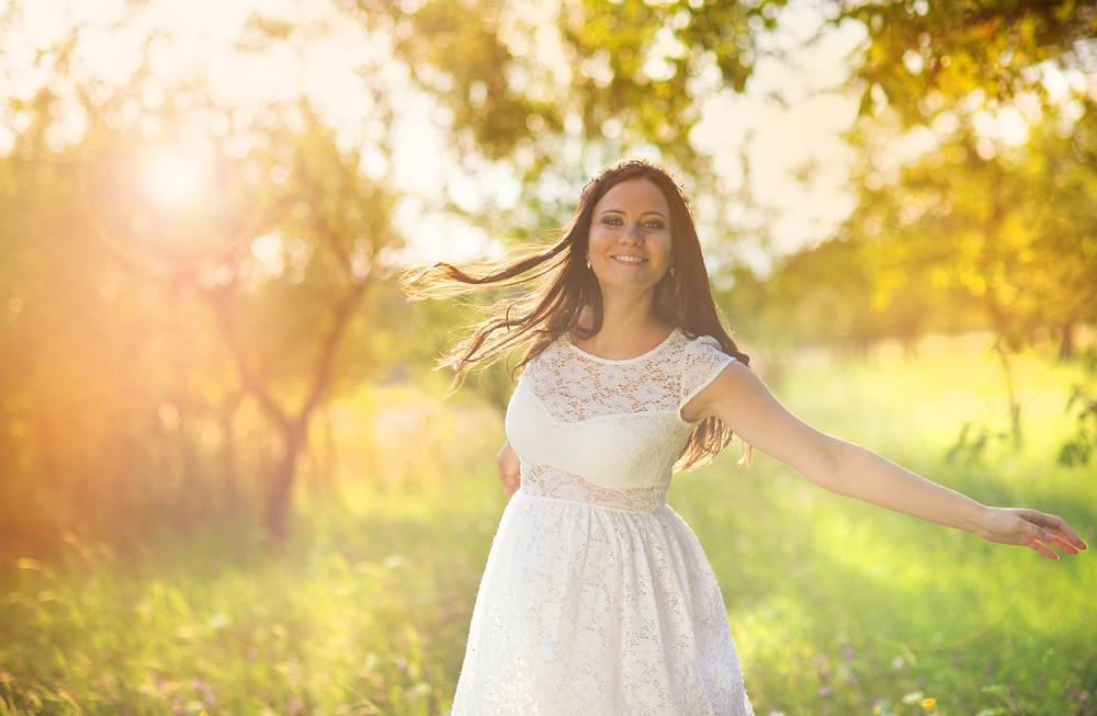 Outdoor natural portrait of beautiful pregnant woman in white dress