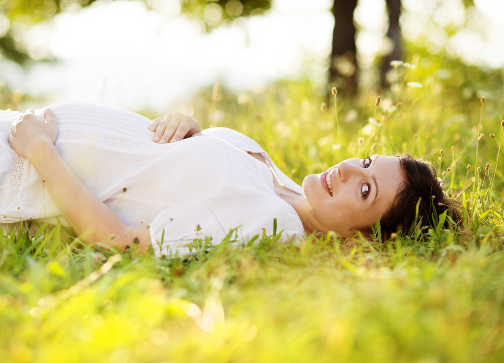 Outdoor natural portrait of beautiful pregnant woman