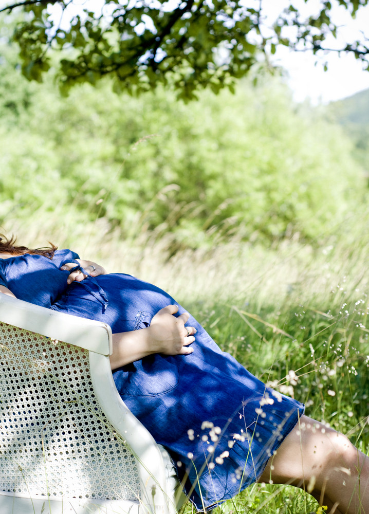 Outdoor natural portrait of unrecognizable pregnant woman relaxing on armchair