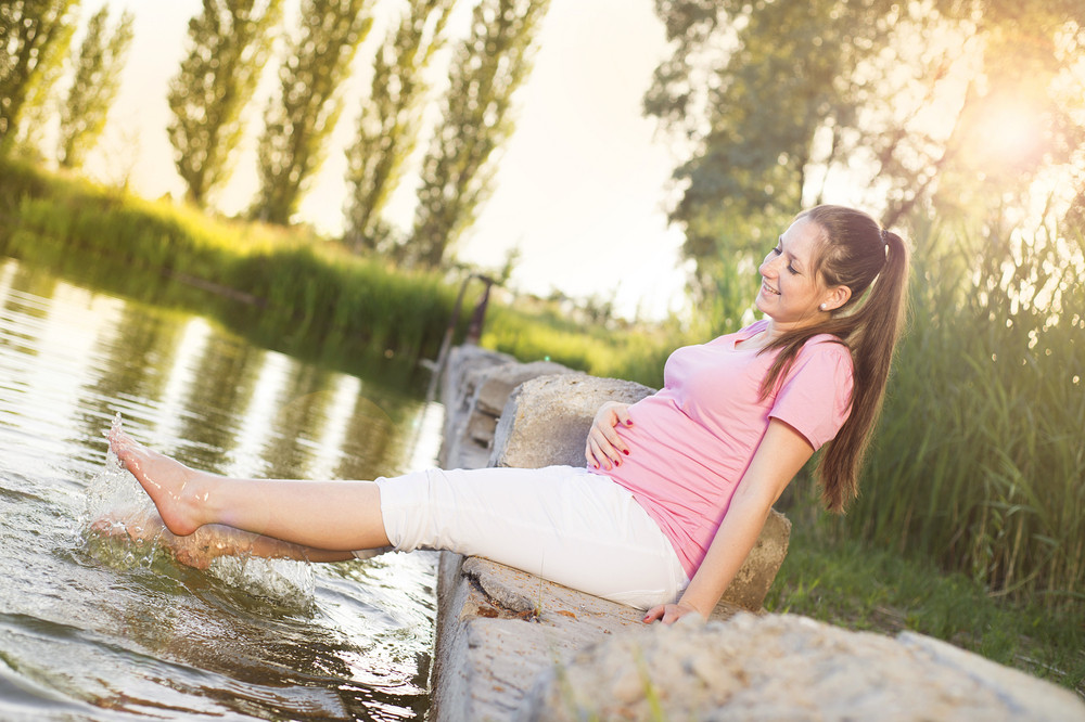 Outdoor portrait of beautiful pregnant woman holding her belly and relaxing by the lake