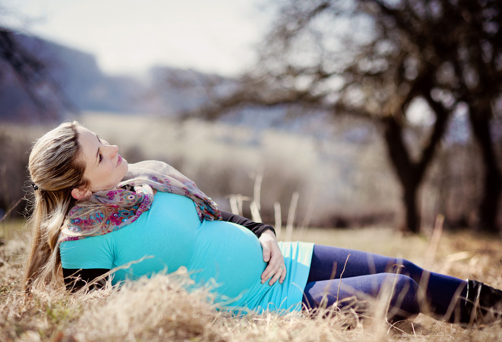 Outdoor portrait of beautiful pregnant woman holding her belly