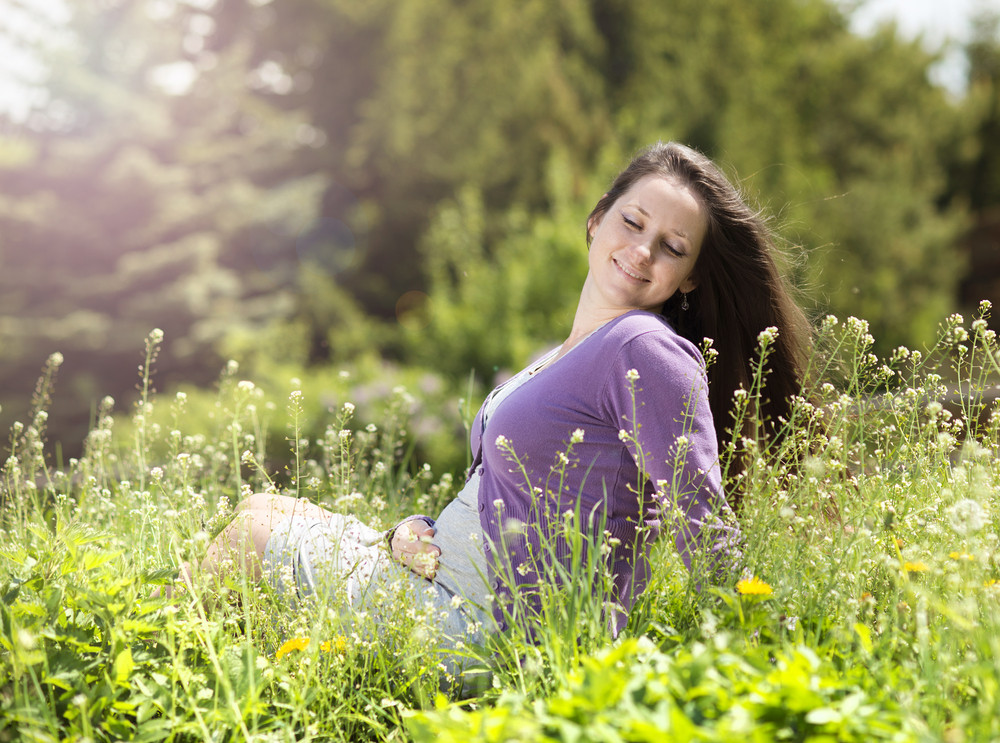 Outdoor portrait of beautiful pregnant woman sitting in green meadow and holding her belly