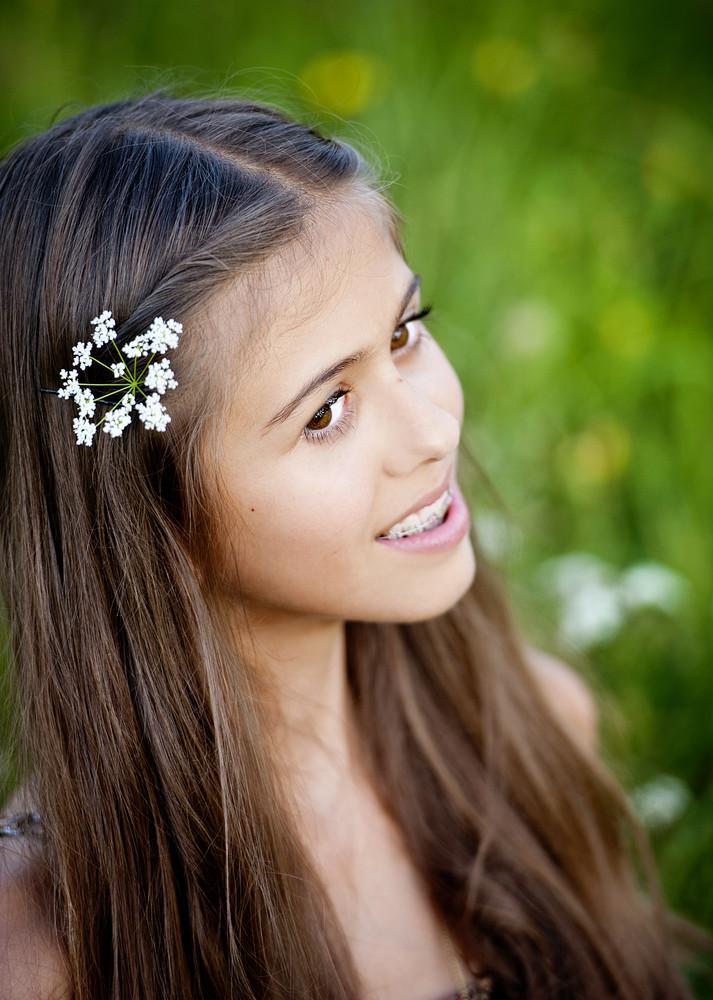 Outdoor portrait of beautiful teenage girl in sunny green meadow