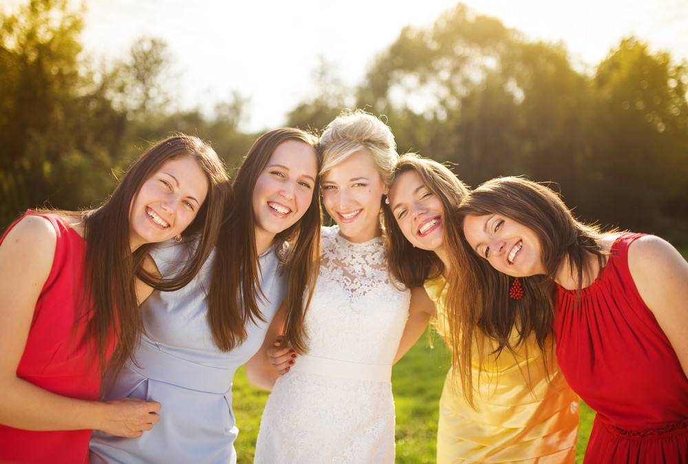 Outdoor portrait of beautiful young bride with her female friends