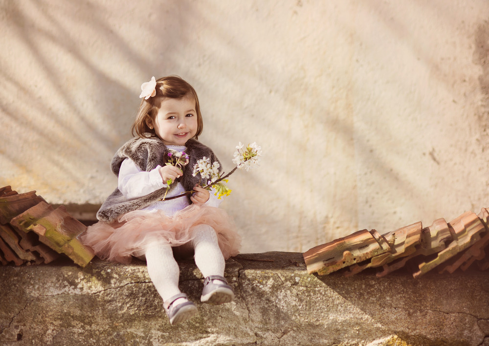 Outdoor portrait of cute little girl sitting on the old roof top