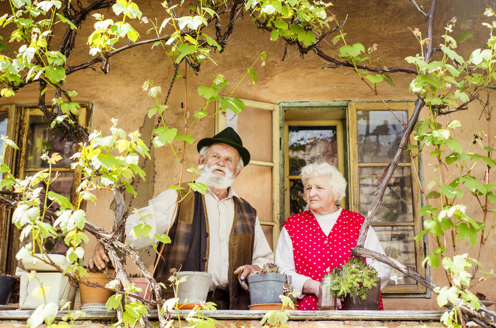 Outdoor portrait of old couple standing by their village house