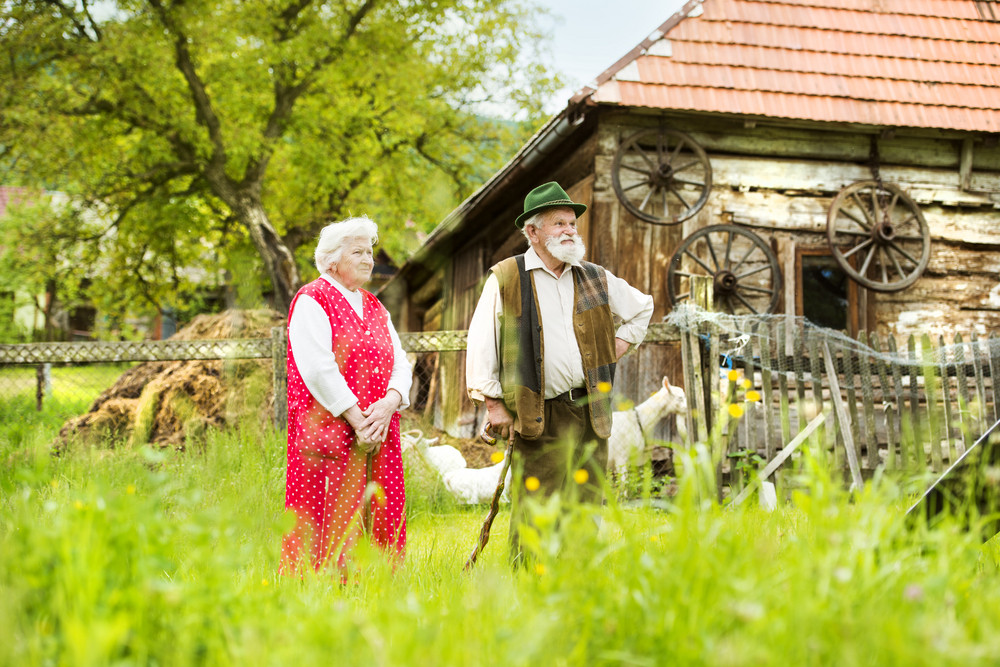 Outdoor portrait of old farmers couple standing by their farmhouse