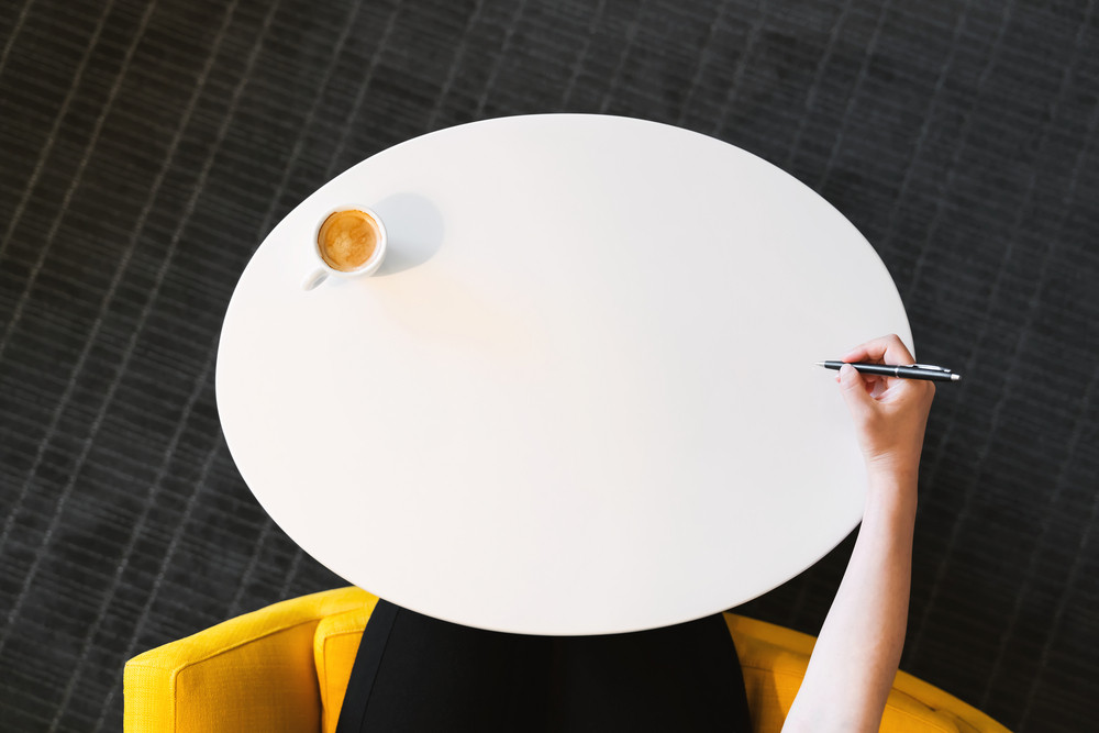 Overhead view of person using a pen in a modern style interior