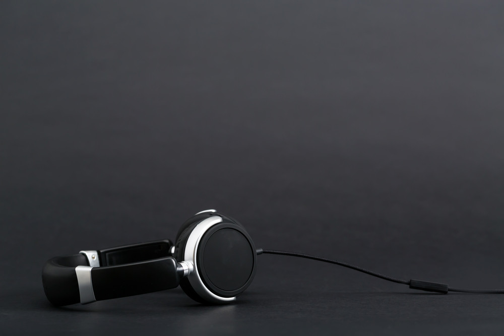 Pair of black headphones on a black background