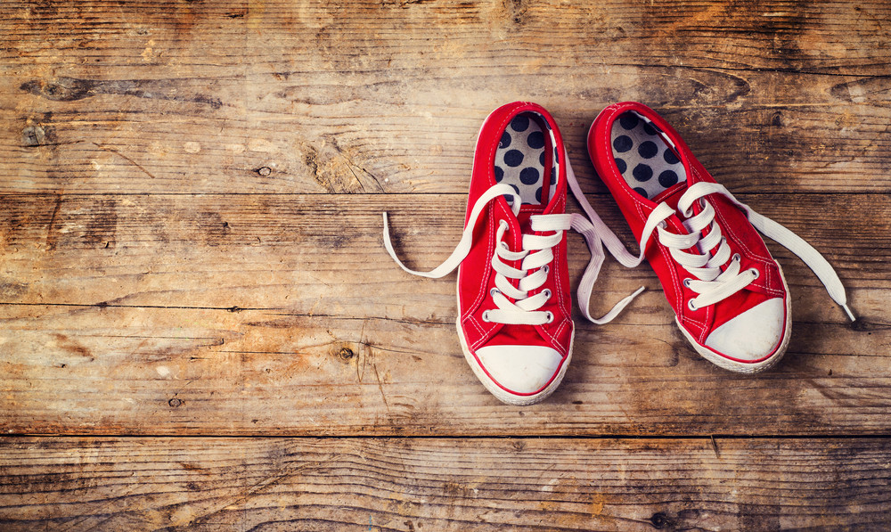 Pair of red sneakers on a floor. Studio shot on a wooden background.