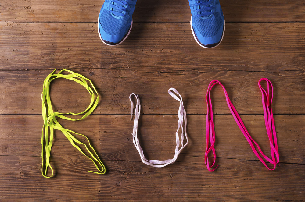 Pair of running shoes and shoelaces run sign on a wooden floor background