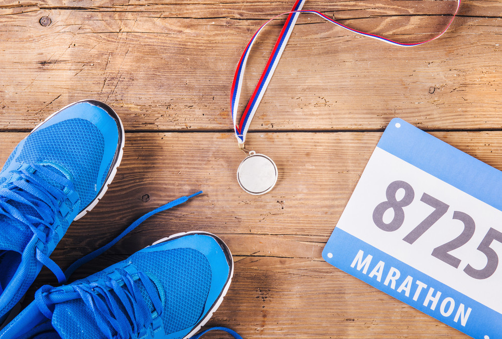 Pair of running shoes, medal and race number on a wooden floor background