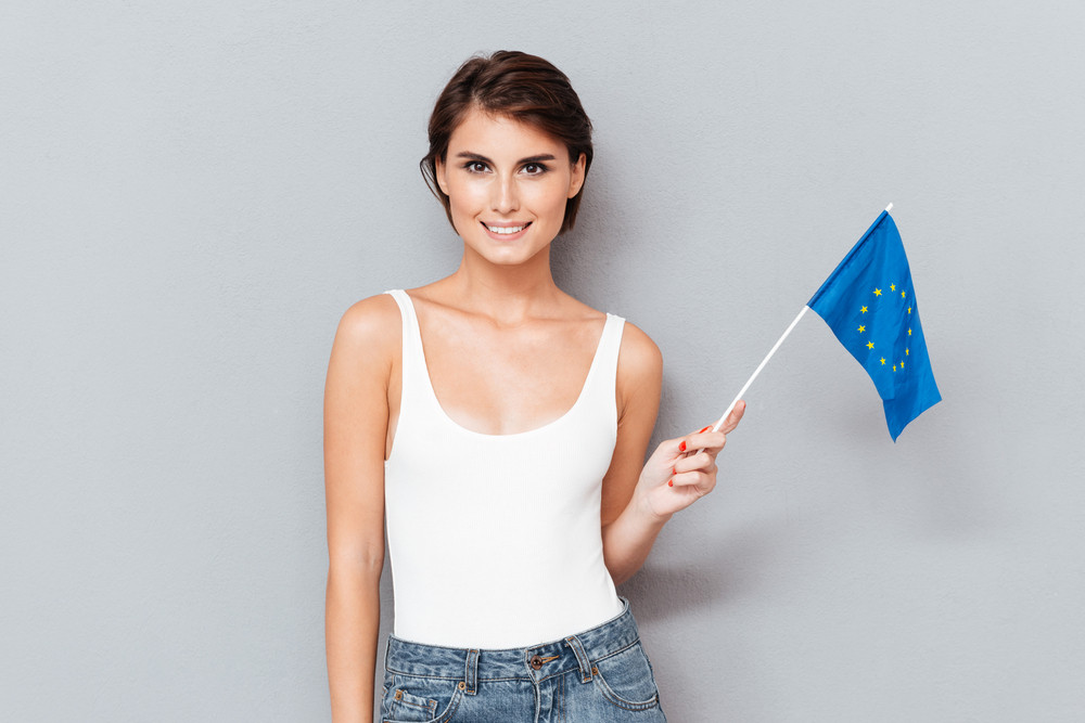 Patriotic smiling woman holding european flag over gray background