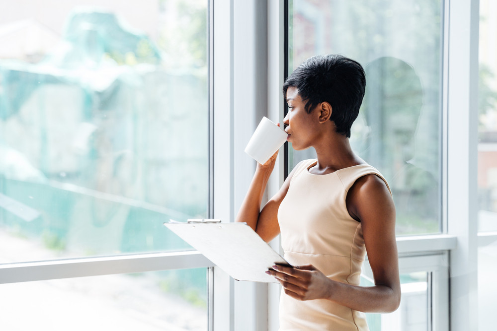 Pensive african american young businesswoman with clipboard drinking coffee and looking at the window in office