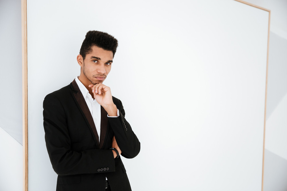 Pensive African business man in black suit in office and looking at camera