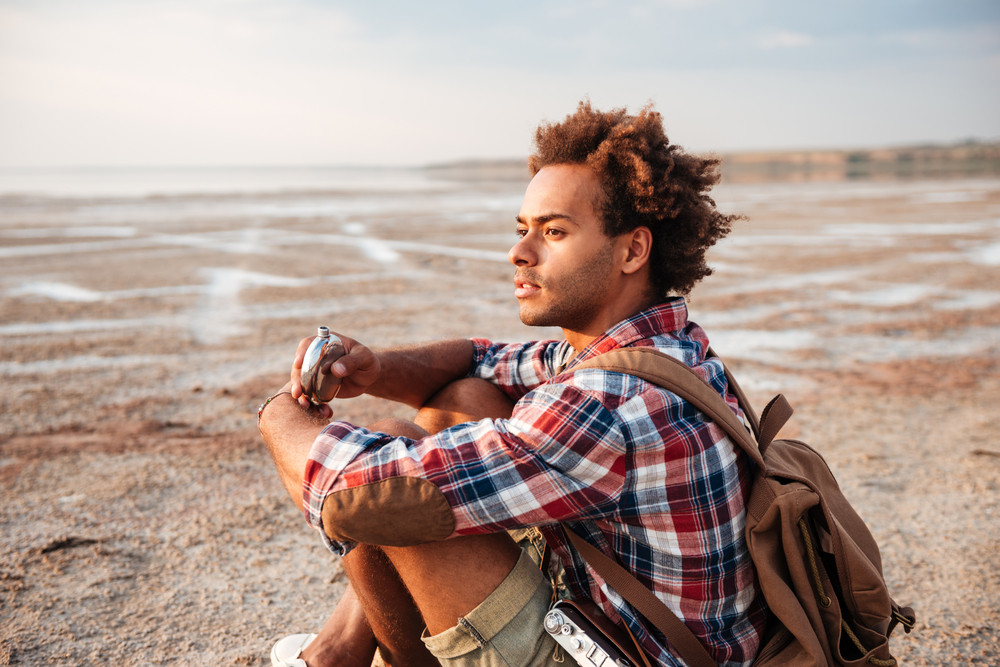 Pensive african young man with backpack sitting and drinking from hip flask