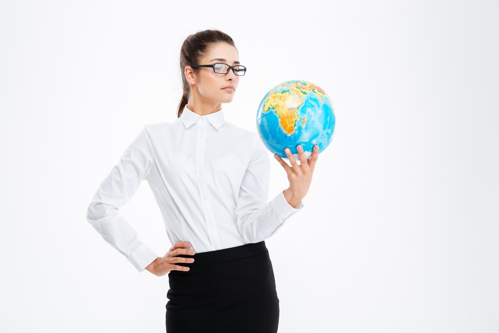 Pensive attractive young business woman holding earth globe