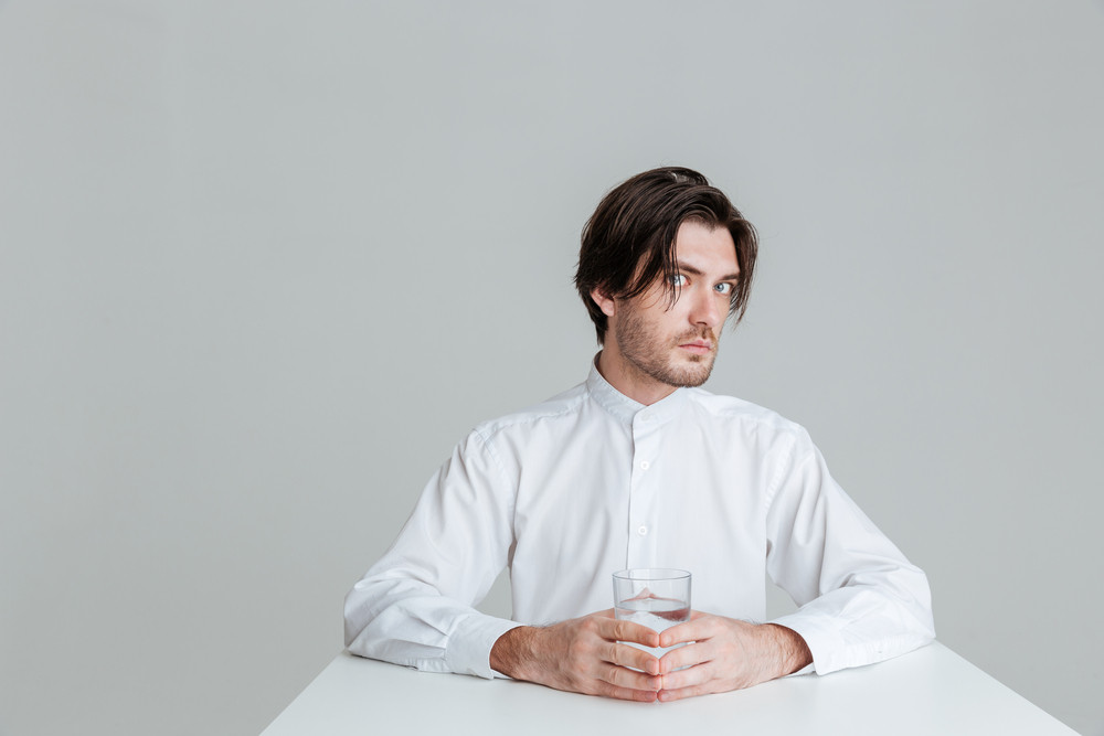 Pensive brunette man with eyes wide open sitting at the table holding water glass isolated on the gray background
