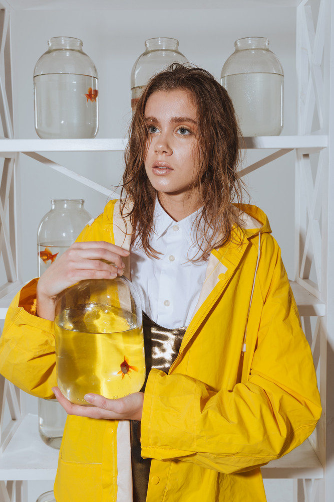 Pensive cute young woman in yellow raincoat holding jar with gold fish