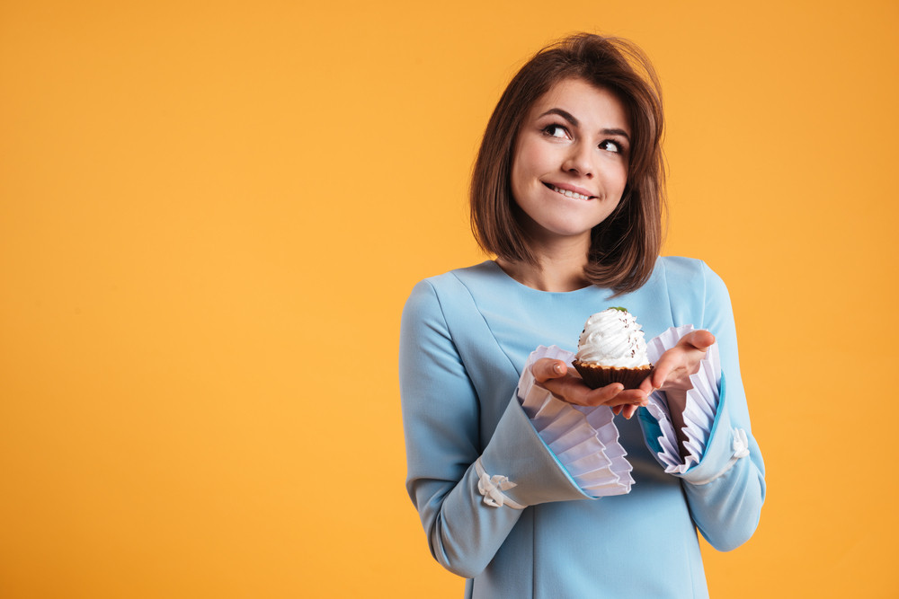 Pensive smiling young woman holding cupcake and thinnking over yellow background