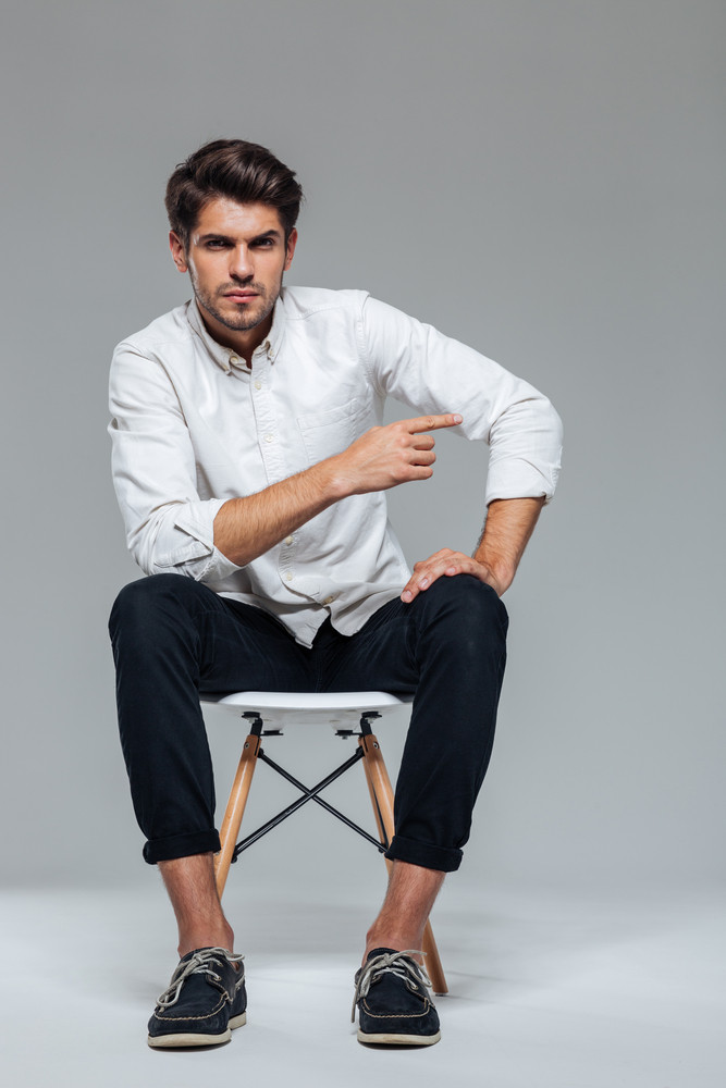 Pensive young bristled man sitting on the chair and pointing finger away isolated on a gray background