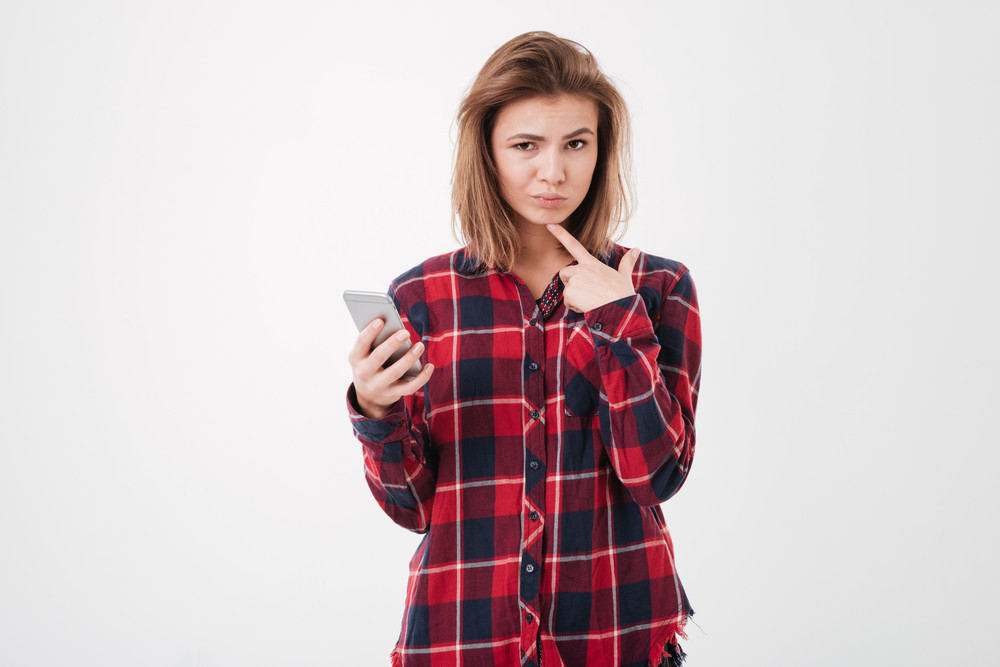 Pensive young cute girl in plaid shirt holding smartphone and looking at camera over white background