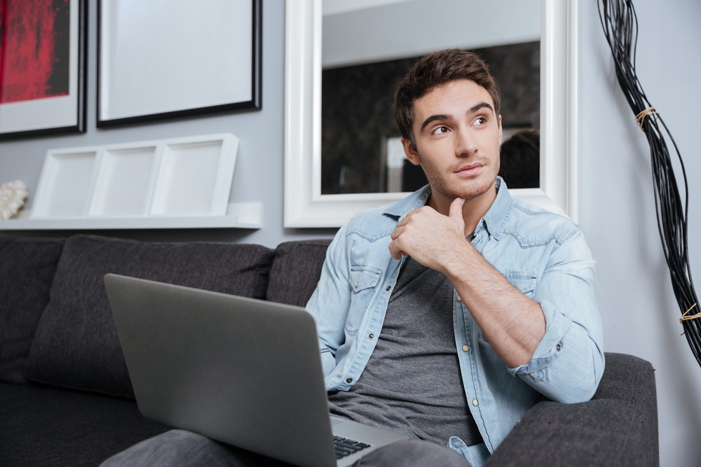 Pensive young man working with laptop and looking away while sitting on sofa at home