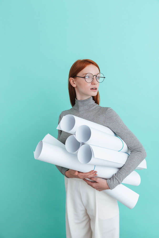 Pensive young woman in round glasses standing and holding blueprints over blue background