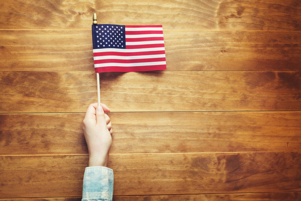 Person holding an American flag on wooden table