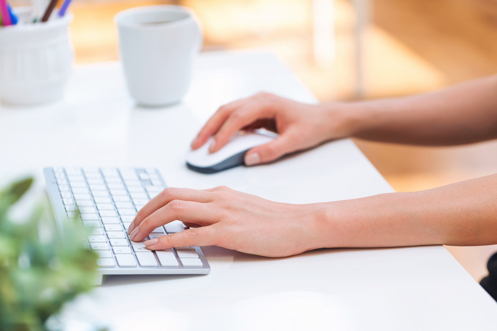 Person typing at on her office computer keyboard