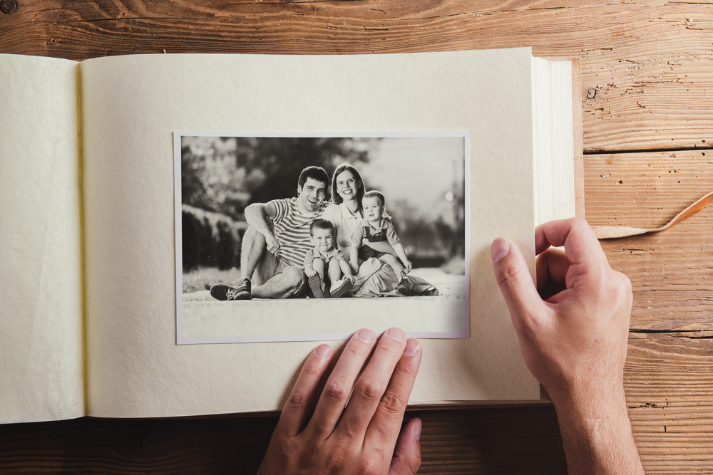 Photo album with black and white family pictures. Studio shot on wooden background.