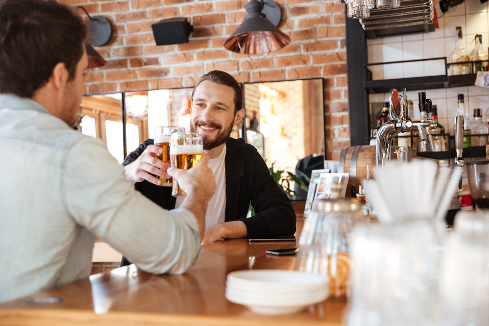 Photo from back of man with smiling friend drinking beer on bar
