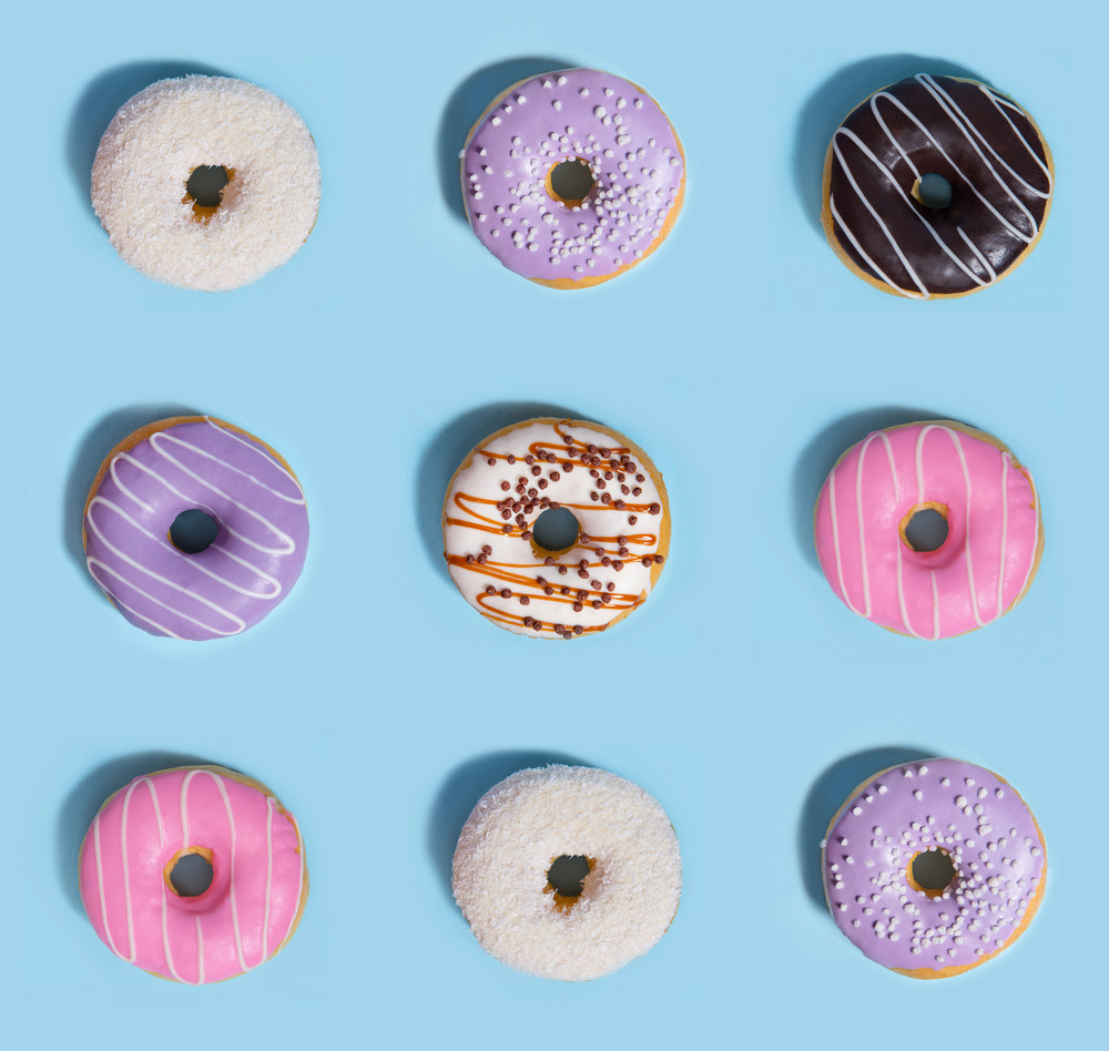Photo of a nine colorful sweeties donuts over blue table background.