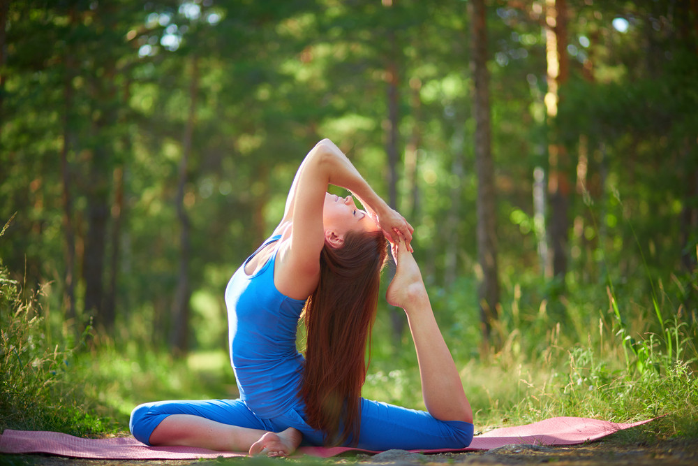 Photo of active and fit girl doing stretching exercise in natural environment