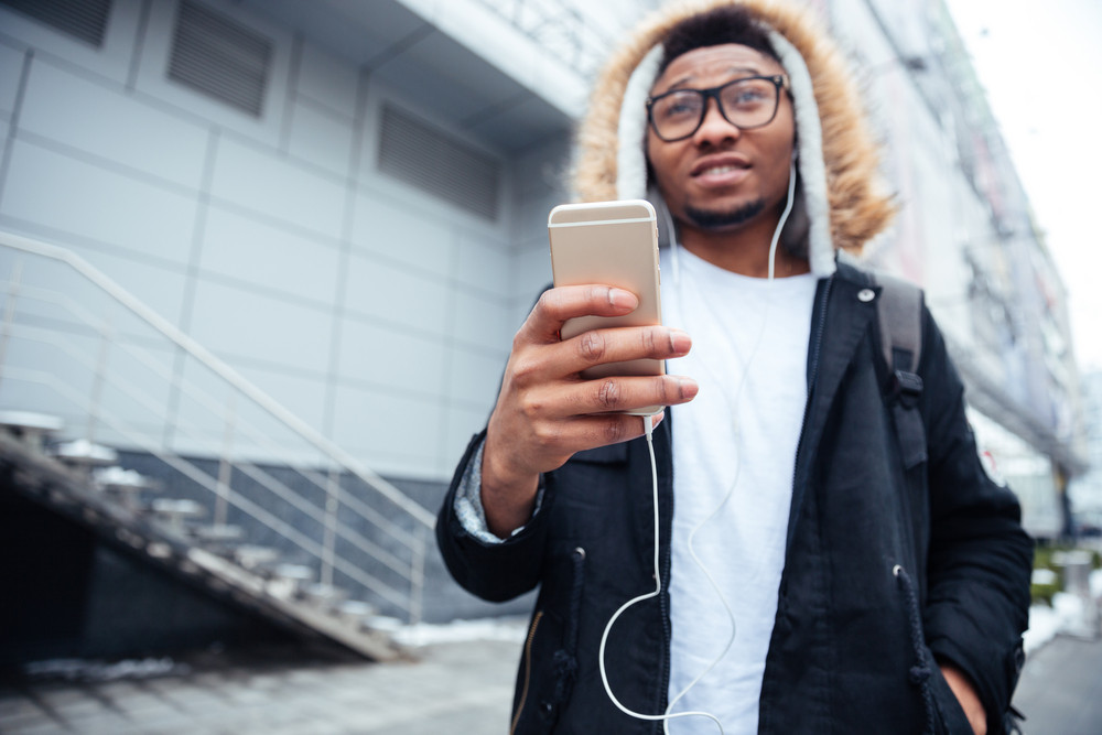 Photo of african handsome man holding his cellphone in hands and chatting while listen to music. Focus on phone.