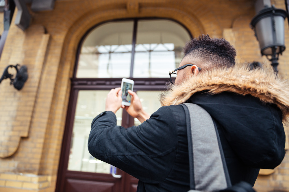Photo of african man holding his cellphone in hands and make a selfie outdoors. Back view.