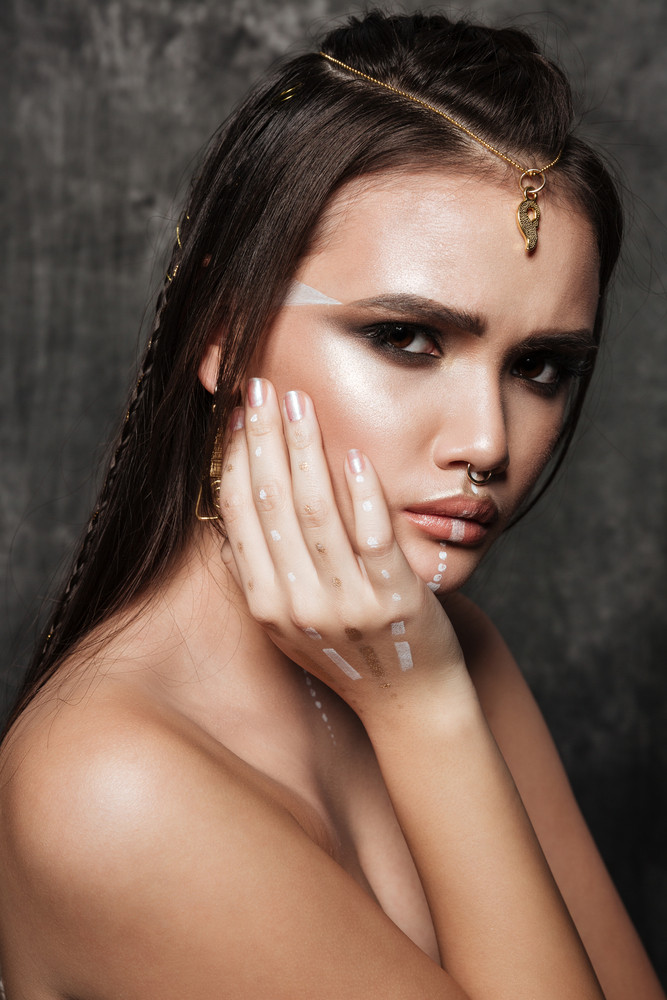 Photo of amazing asian model with bright makeup and sunburn skin touching face with hands. Look at camera.