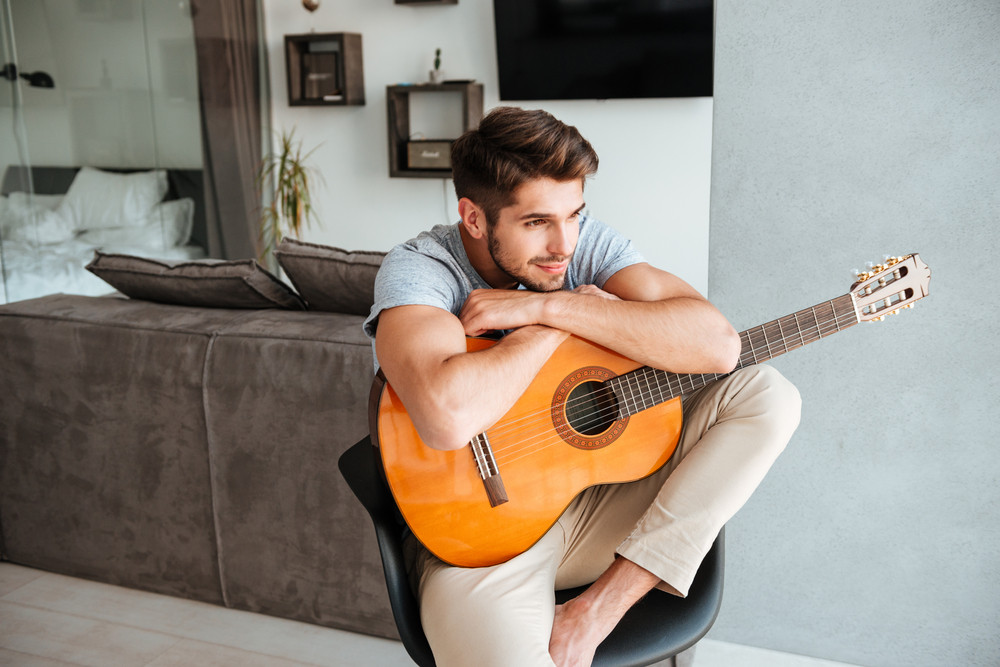 Photo of attracrive man sitting with guitar on chair and look aside.