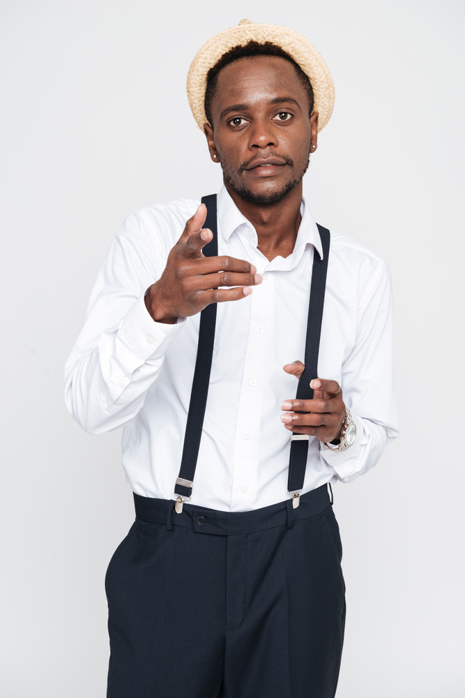 Photo of attractive african man wearing hat posing in studio and pointing. Isolated over white background. Look at camera.