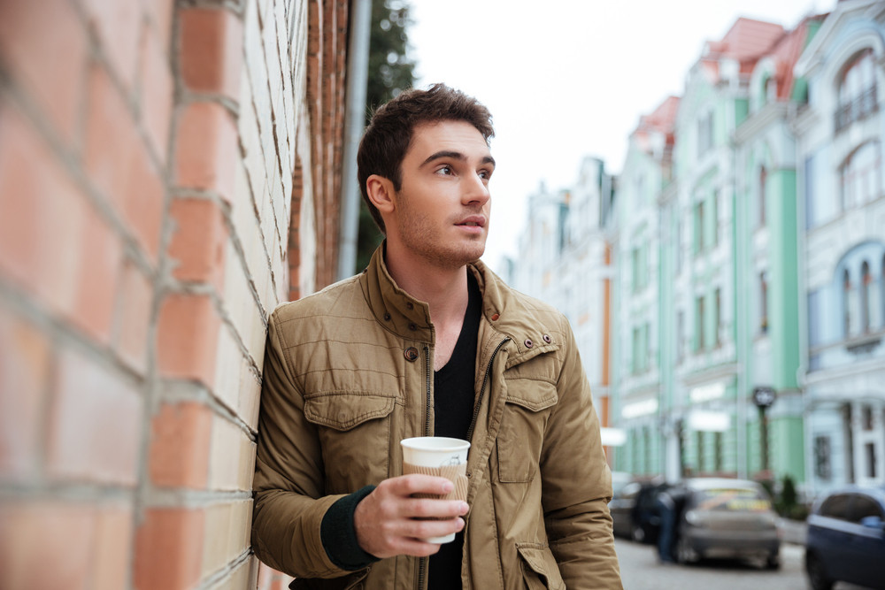 Photo of attractive serious young man walking on the street and looking aside while holding cup of coffee.