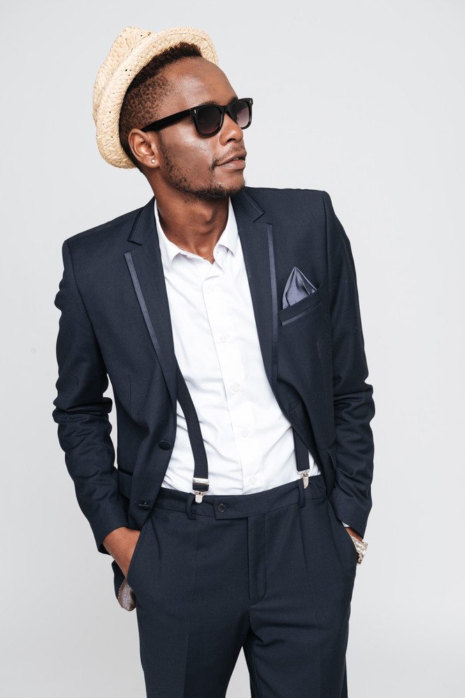 Photo of attractive young african businessman wearing hat posing in studio. Isolated over white background. Look aside.
