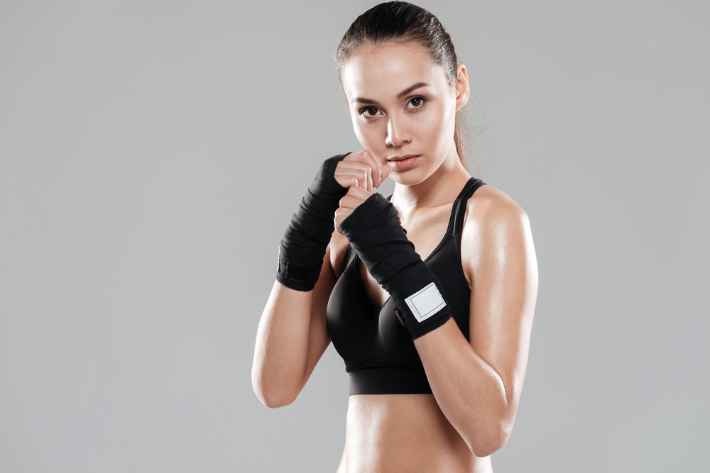 Photo of attractive young boxer lady posing over grey background.