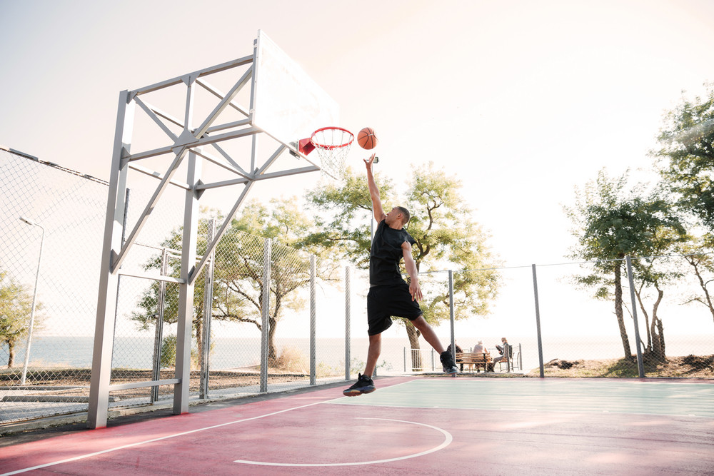 Photo of basketball player practicing and posing for basketball and sports athlete concept. Looking at basketball hoop.