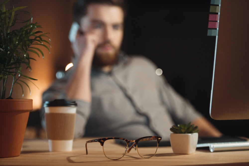 Photo of bearded designer dressed in shirt in a cage working in office late at night and talking by phone near glasses and cup of coffee. Focus on glasses.
